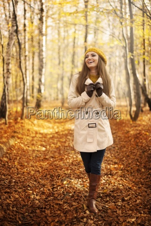 smiling woman walking in park at