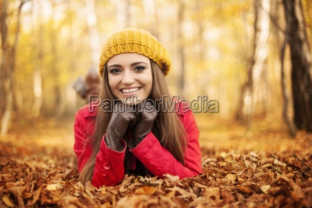 smiling woman lying down on autumn