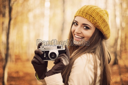 smiling, young, woman, holding, retro, camera - 12109936