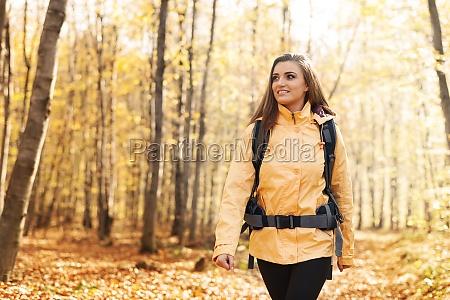 smiling woman wearing yellow jacket walking