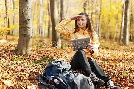 female hiker has break and looking