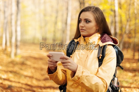 confused young hiker with smart phone