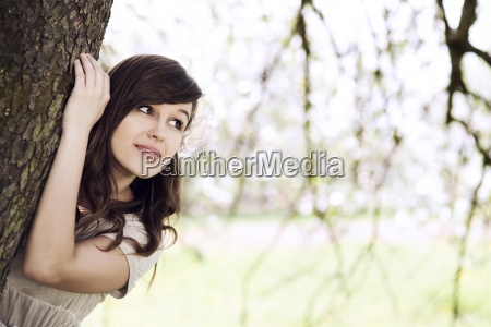 beautiful young woman hiding behind tree