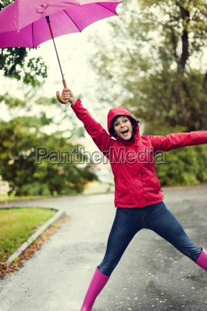 cute young woman jumping with umbrella