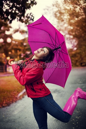 cheerful woman with umbrella and rubber