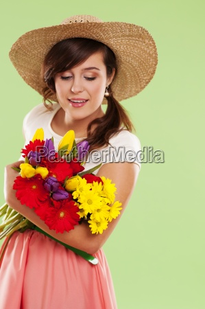 woman wearing straw hat holding spring