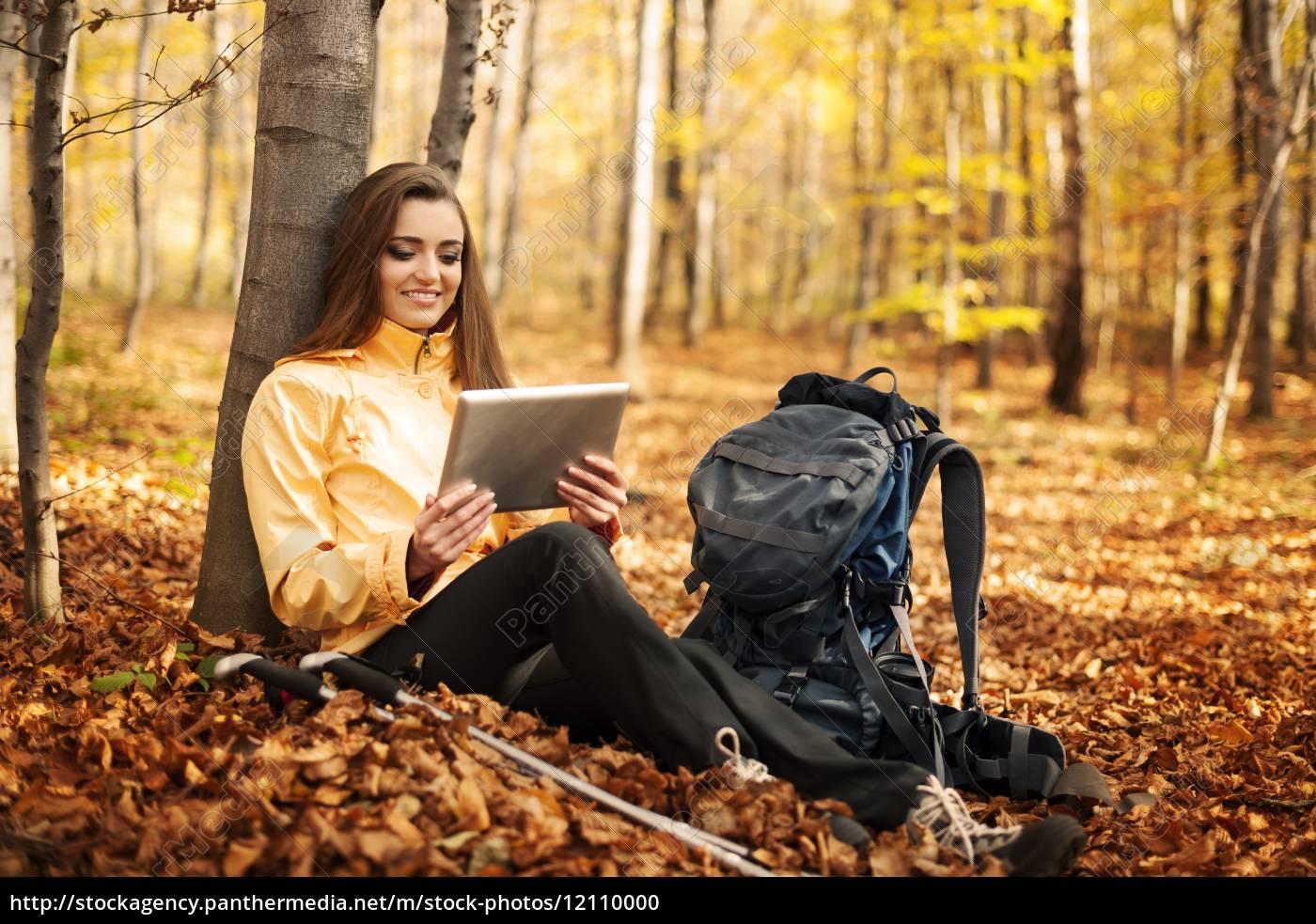 sitting, female, hiker, using, digital, tablet - 12110000