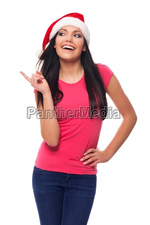 happy woman wearing santa hat pointing