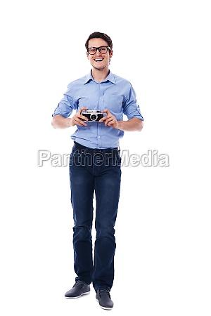 man wearing glasses holding vintage camera