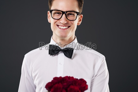 man wearing on glasses holding bouquet