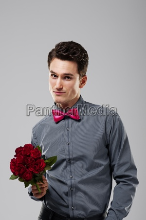 handsome man holding red roses