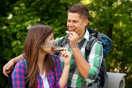 young couple eating chocolate in forest
