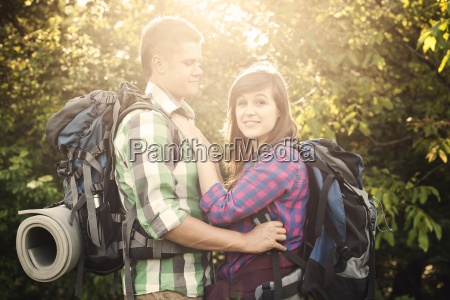 loving couple in forest at sunset