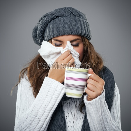 young woman having flu and blowing