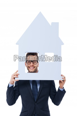 smiling businessman holding house sign