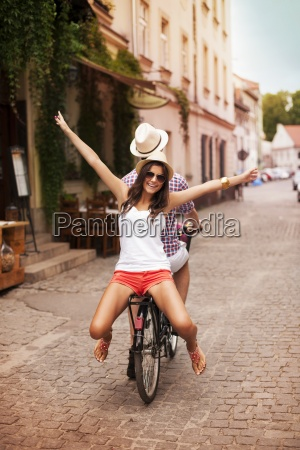 happy young woman riding on bicycle