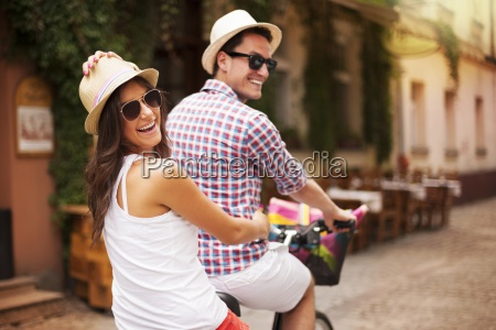 happy couple riding a bicycle in