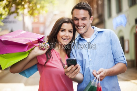 happy couple using smart phone during
