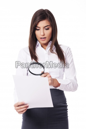 shocked woman looking through a magnifying