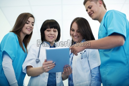 medical team checking results on digital