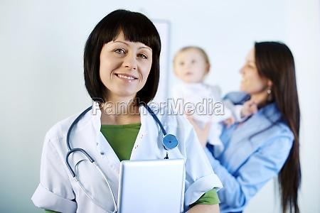 smiling doctor holding tablet