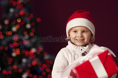little girl holding red gift box