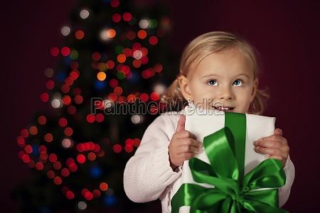 little girl holding christmas gift