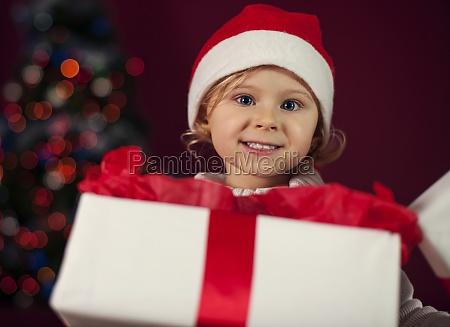 santa little girl opening christmas present