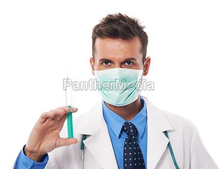 portrait of confident surgeon holding syringe