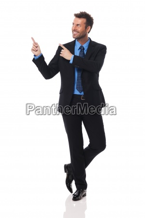 handsome and smiling businessman pointing at