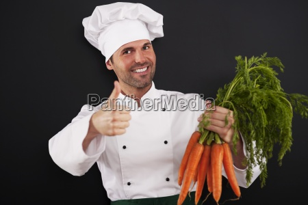 chef with bunch of carrots showing