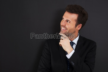 young businessman peeking at empty blackboard