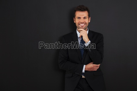 handsome businessman standing at the blackboard