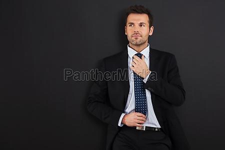 focus businessman wearing tie against blackboard