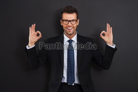 happy businessman wearing glasses showing ok