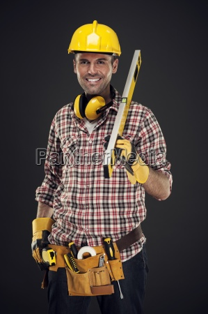 smiling construction worker holding measuring