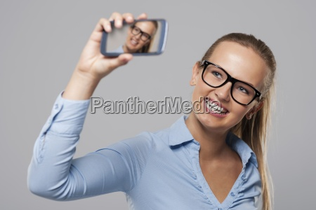 blonde businesswoman wearing glasses taking self