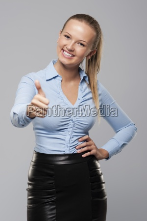 smiling young businesswoman showing thumb up
