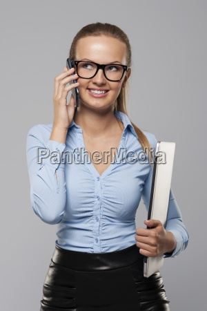smiling blonde businesswoman holding laptop and