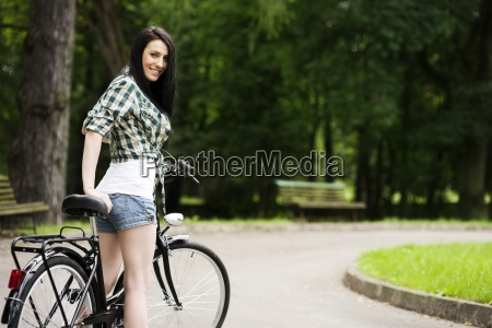 beautiful young woman with bicycle in