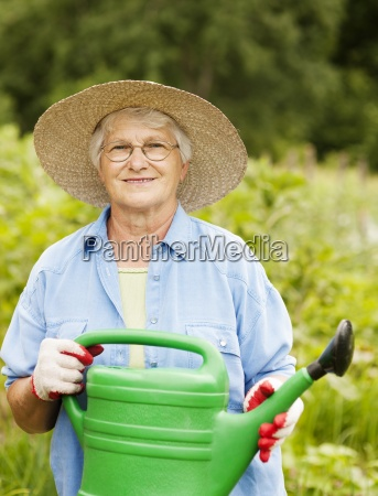 senior woman holding watering can