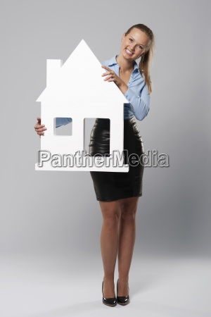 smiling, young, woman, holding, house, sign - 12117570