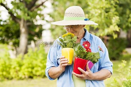 senior woman smelling flowers
