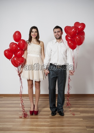 smiling couple with balloons holding hands