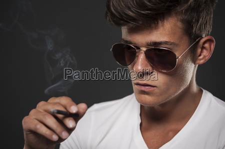 focus young man with black cigarette
