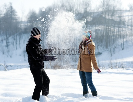 young couple playing with snow
