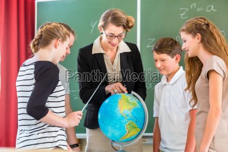 teacher teaches students a class in