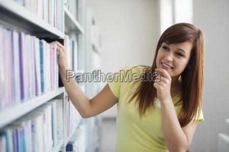 beautiful student choosing book in library