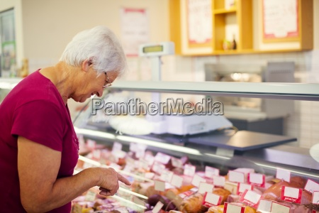 senior woman in butchers shop