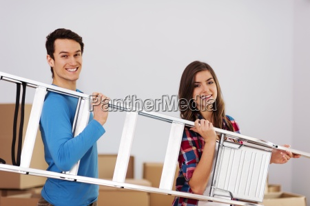 young happy couple with a ladder